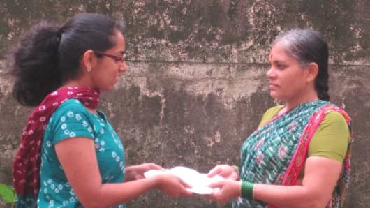 Saigal explains how the pads work to a woman at Saathi's pilot village in India.
